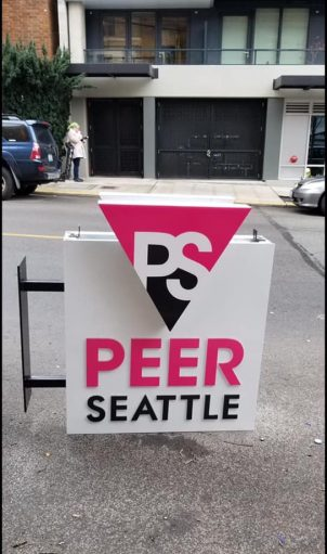 The non-profit formerly known as SASG (Seattle Area Support Group) is now PEER SEATTLE and install a new sign at their new location to reflect that. Photo by Marc Shelffo  via Tony Radovich/Facebook