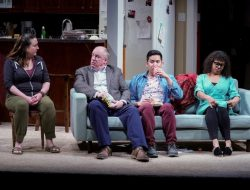 The cast of Cheryl Strayed's TINY BEAUTIFUL THINGS onstage at Seattle Rep through June 29, 2019: Julie Briskman, Charles Leggett, Justin Huertas and Chantal DeGroat examining what might be the ugliest top in history while sitting on the stupidest family room couch choice in history.